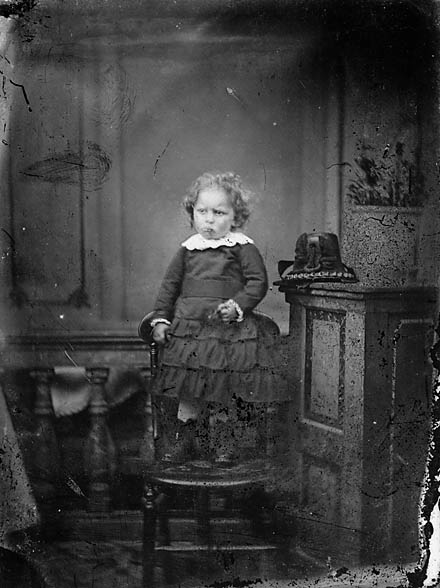 [A young girl standing on a chair]
