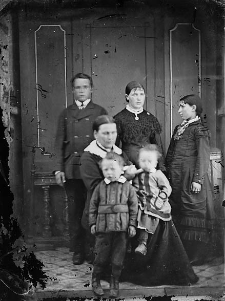 [Three women, a young man and two children]