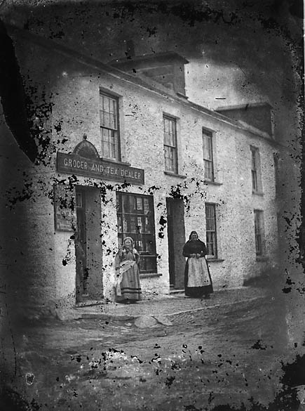 [Two women standing outsied a grocer's shop]