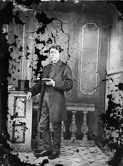 [A young man standing and reading a book]