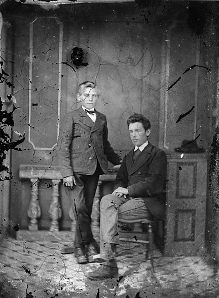 [Two young men, one standing and the other sitting]