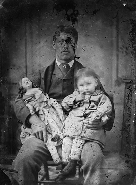 [A man holding a child and a doll]