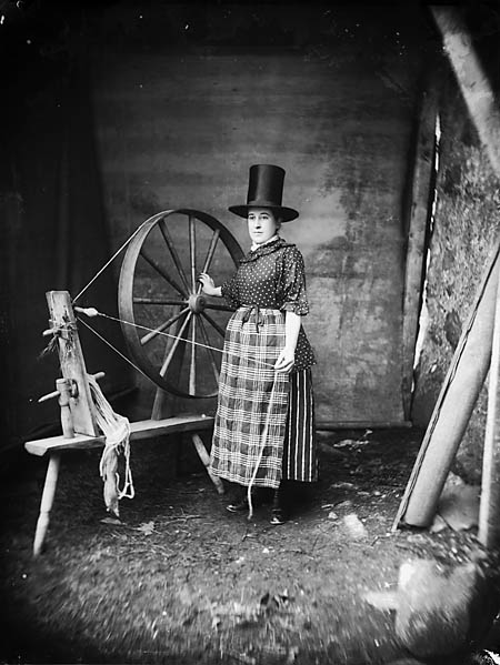 "[A woman in ""Welsh national"" dress with a spinning wheel]"