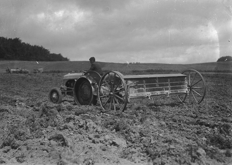 [Man on tractor pulling agricultural implement]