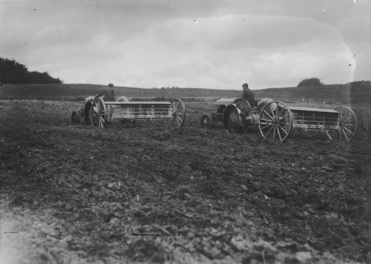 [Men on tractors pulling agricultural implements]