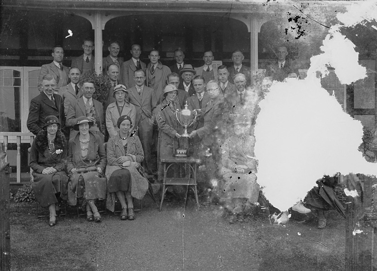 [A group outside Llandrindod Wells Golf Club pavilion for a presentation of a cup]