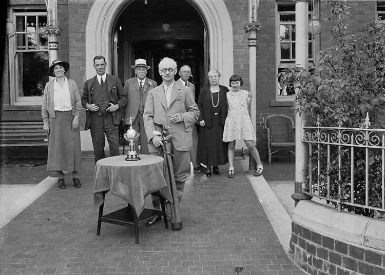 [Middle-aged gentleman holding golf clubs alongside a trophy, with a group of people in the background]