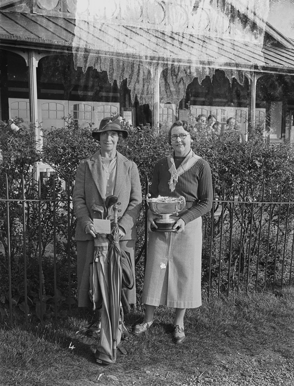 [Two lady golfers outside Llandrindod Wells Golf Club pavilion, one holding a cup]