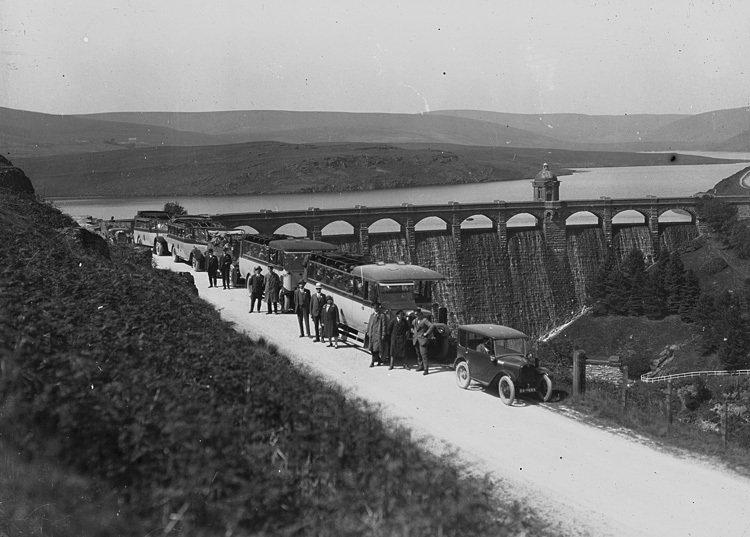 [Men and women in buses and cars visiting a reservoir in Elan Valley]