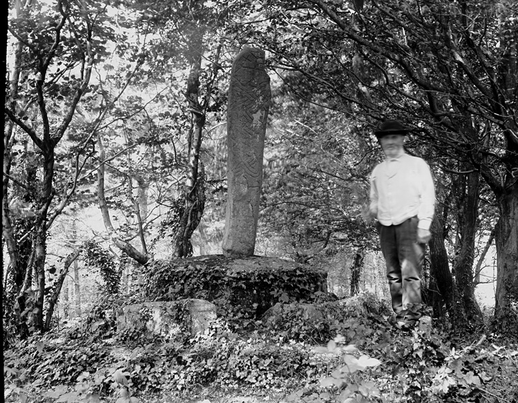 [Man standing aside monument]