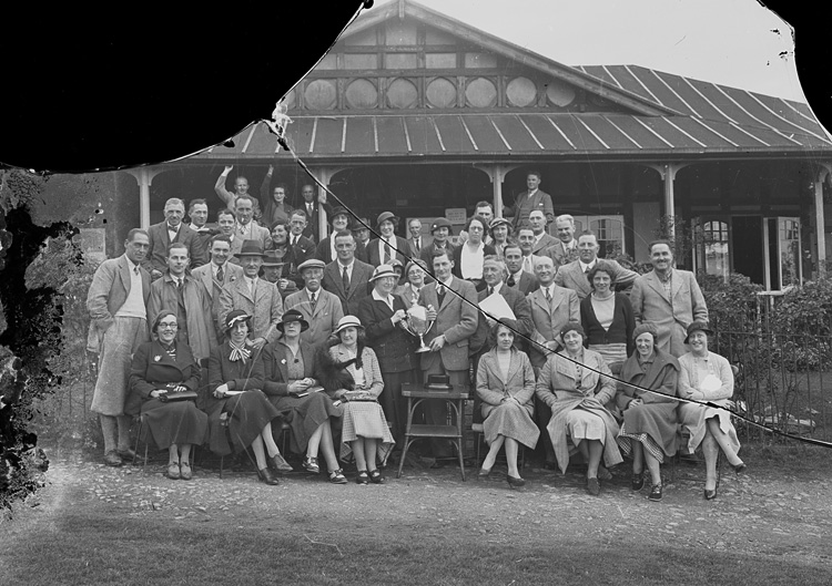 [Group of golfers outside Llandrindod Wells Golf Club pavilion, one being presented with a cup]