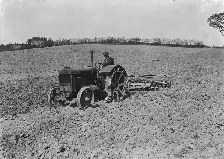[Man harrowing with tractor and disk harrow]