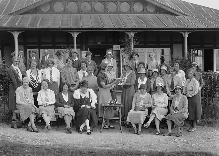 [Group outside Llandrindod Wells Golf Club pavilion, with a lady golfer being presented with a cup]