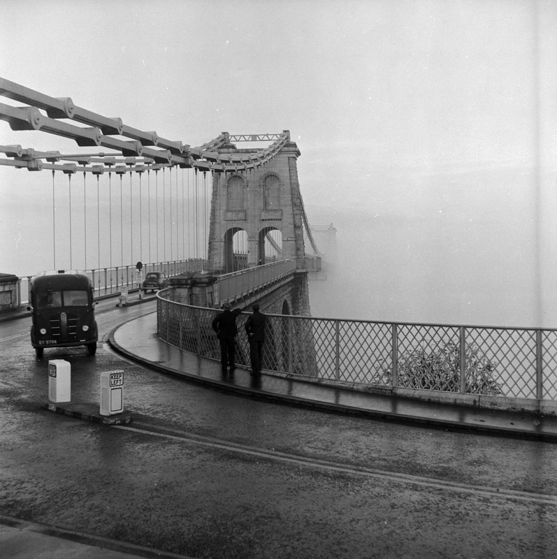 "[Menai Suspension Bridge, Menai Bridge, which appears to be ""cut in half"" by thick fog]"