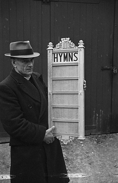 [Rev. J.H. Bloomer with the hymn board he carved for Llandyssil Church in memory of Rupert Matthias]