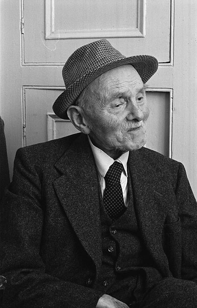 An old man in a  jacket, waistcoat and tweed  hat