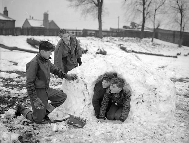 [Children building an igloo in the snow]
