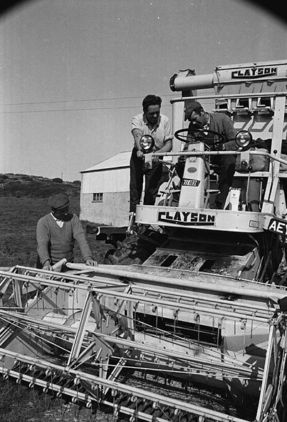 Three men and a Clayson combine harvester