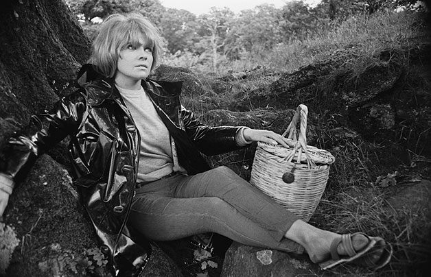 Woman in a PVC jacket posing with a picnic basket