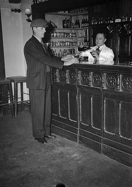 [The bar at The Royal Lion Hotel, Dolgellau, together with the hotel's darts team]