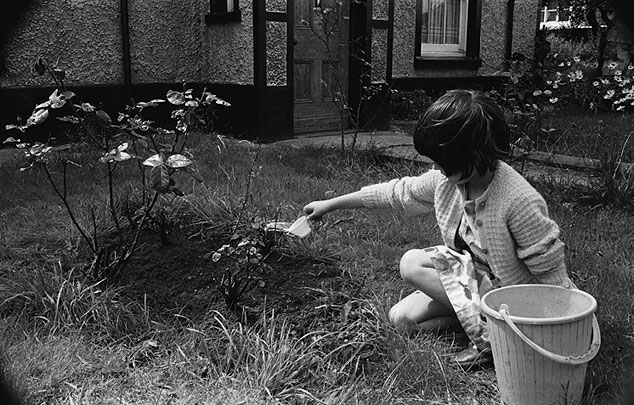 A young girl watering plants in a garden