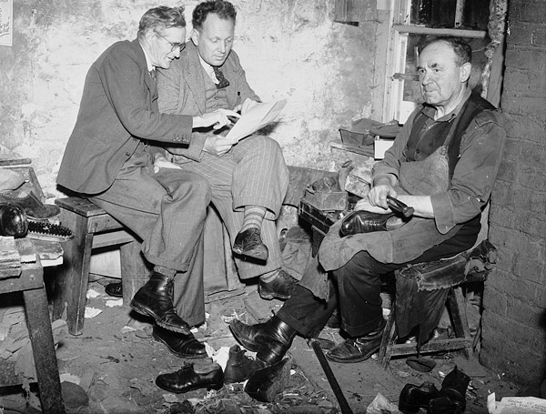 [Evan Jenkins and David Jones, two folk poets from Ffair-Rhos, discussing their poems in a cobbler's workshop]