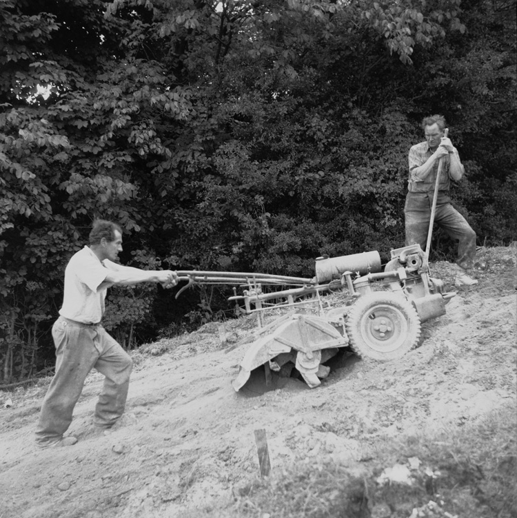 [Two men using a rotovator]