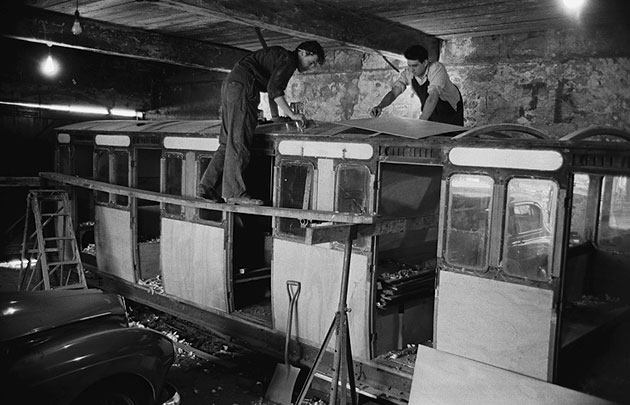 Two men restoring an old train carriage