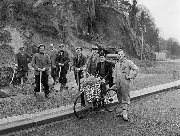 [Daniel Tanguy, an onion seller from Roscoff, Brittany, with road workers near Pont Gwenyn y Meirch, Llanycil]