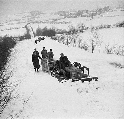 [A bulldozer, tractor and sledge deliver bread to the snowbound village of Llanwddyn]