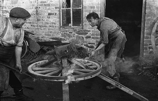 [Fred and George Owen putting a rim on a wheel at Glanrafon, Tanat Valley, Montgomeryshire]