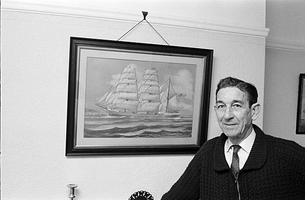 Man next to a painting of a ship