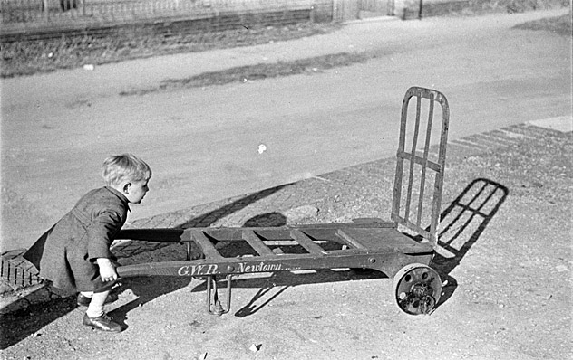 A young boy with a railway luggage carrier